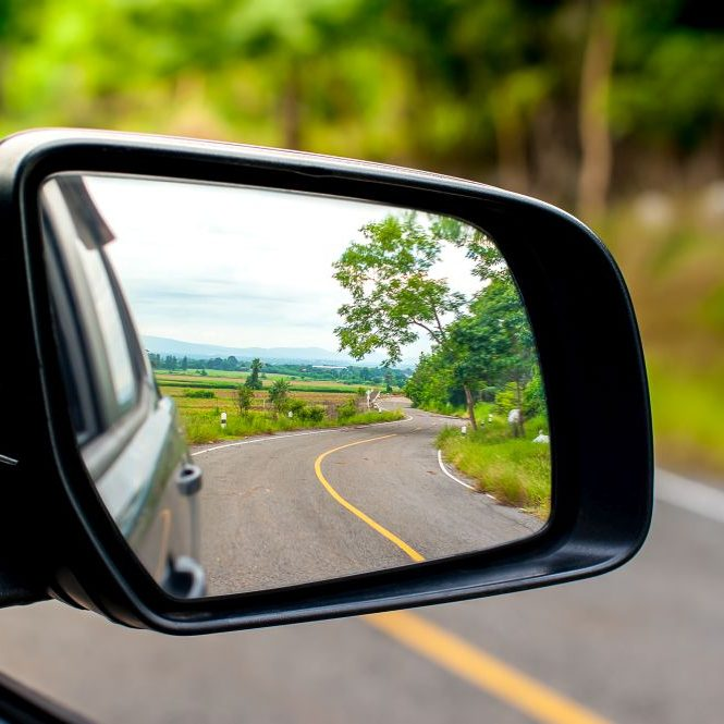 Landscape in the sideview mirror of a car , on road countryside.